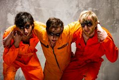 Three guys in orange uniforms Stock Images