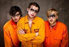 Three guys in orange uniforms. Indoors Stock Photo