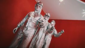 Three guys in silver overalls, hard hats and goggles snaps fingers in rhythm stock video