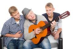 Three guys spend leisure playing guitar. Three friends spend leisure playing guitar. Two of the boys twin brothers Stock Photos