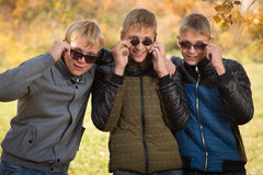 Three guys in sunglasses in autumn park Stock Images