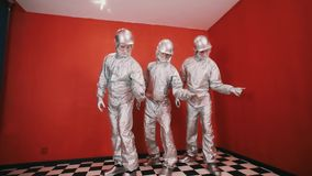 Three guys in tin foil overalls, hard hats and goggles snaps fingers in rhythm stock footage