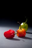 Three Habanero Peppers. On dark background. One red, one orange and one green with stems Stock Photo