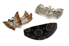 Three hair clips against a white backdrop. A photo taken on three hair clips against a white background. The designs are black, floral and butterfly Stock Photos