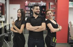 Three hairdressers posing in barber shop Royalty Free Stock Photo