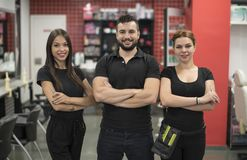 Three hairdressers posing in barber shop Stock Images