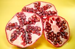 Three halfs of pomegranate on yellow background, horizontal shot. Picture presents three halfs of pomegranate on yellow background, horizontal shot Royalty Free Stock Images