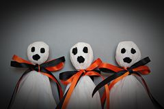 Three halloween ghosts DIY made from white tissue paper, black and orange ribbon on gray background Royalty Free Stock Photography