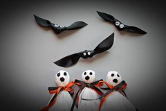 Three halloween ghosts and three bats on gray background Stock Photo