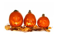 Three Halloween Jack o Lanterns with autumn leaves isolated Royalty Free Stock Images
