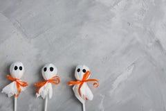 Three halloween lollipop ghosts on gray concrete background Stock Photo