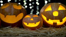 Three halloween pumpkins with eerie faces burning . Black bokeh background. Close up