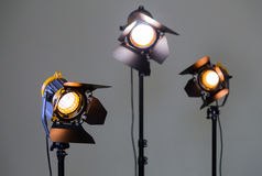 Three halogen spotlights with Fresnel lenses on a grey background. Photographing and filming in the interior. Lighting equipment for movie production royalty free stock photography