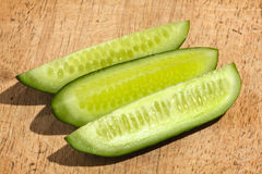 Three halves of cucumber on wooden cutting board Stock Photo