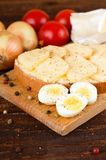 Three halves of quail eggs on chopping board Stock Photo