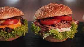 Three hamburger variety - appetizing beef, pulled pork and chicken sandwich in a row. With delicious ingredients - camera slide in front stock video footage
