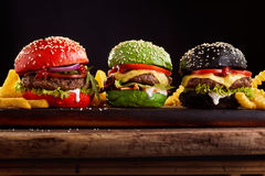 Three, hamburgers on colorful bred buns. In red , green and black giving assorted options of filling viewed from the side on a wooden board royalty free stock photo