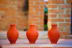 Three handmade clay jug on brick wall background Stock Photography