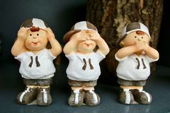 Three handmade figurines that represent: hear, see and remain silent. Three handmade figurines of little boys with caps on their heads, which represent: hear Stock Photos