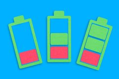 Three handmade paper icons of batteries from low to full in center of blue table. Top view vector illustration