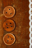Three handmade wooden bottons on old table royalty free stock photography