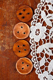 Three handmade wooden buttons on old table and lace Stock Photo