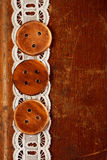 Three handmade wooden buttons on old table and lace Stock Image