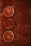 Three handmade wooden buttons on old table Stock Image