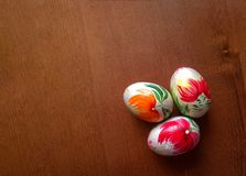 Three handmade wooden easter eggs on wooden. Top view stock photography