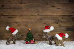 Three handmade wooden reindeer as santa on old wood background f Royalty Free Stock Photography