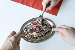 Three hands with three dessert forks stretch to a small strawber Royalty Free Stock Photo