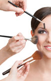 Three hands of makeup artists applying cosmetics Stock Photography