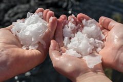 Three hands with natural salt. Natural organic salt from ocean in Hawaii Stock Image