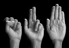 Three hands over black stock image
