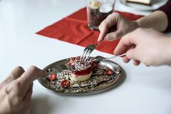 Three hands with three dessert forks stretch to a small strawber Stock Photo