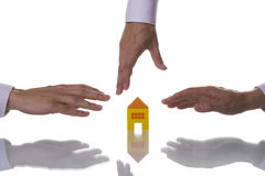 Three hands trying to reach a house Royalty Free Stock Image