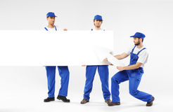 Three handsome builders holding signs Royalty Free Stock Images