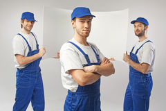 Three handsome employees holding a board Stock Photography