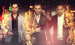 Three handsome men holding a gun. Three burning men holding a gun in front of a city Stock Image