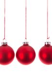 Three hanging Christmas balls at a white background stock photography