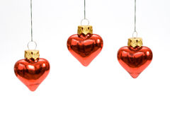 Three hanging red heart shaped. Christmas baubles isolated on white stock photos