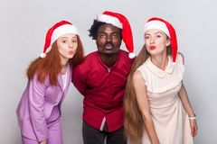 Three happiness friend in red cap, send air kiss at camera. Indoor shot Royalty Free Stock Image