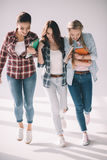 Three happy beautiful girls students with books walking together Stock Image