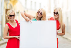 Three happy blonde women with blank white board. Summer holidays, , travel, tourism and advertisement concept - three happy blonde women with blank white board Royalty Free Stock Image