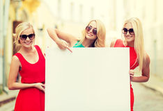 Three happy blonde women with blank white board Royalty Free Stock Images