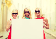 Three happy blonde women with blank white board Stock Photos
