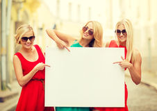 Three happy blonde women with blank white board. Summer holidays, , travel, tourism and advertisement concept - three happy blonde women with blank white board Royalty Free Stock Photography