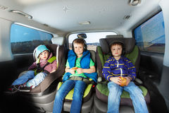 Three happy boys sitting in safety car seats. Three happy boys, age-diverse brothers, sitting in safety car seats, snaking and listening the music during car Royalty Free Stock Photography
