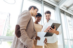 Three happy business people looking through documents together in office Royalty Free Stock Photos