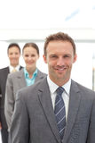 Three happy business people posing in a row Royalty Free Stock Image